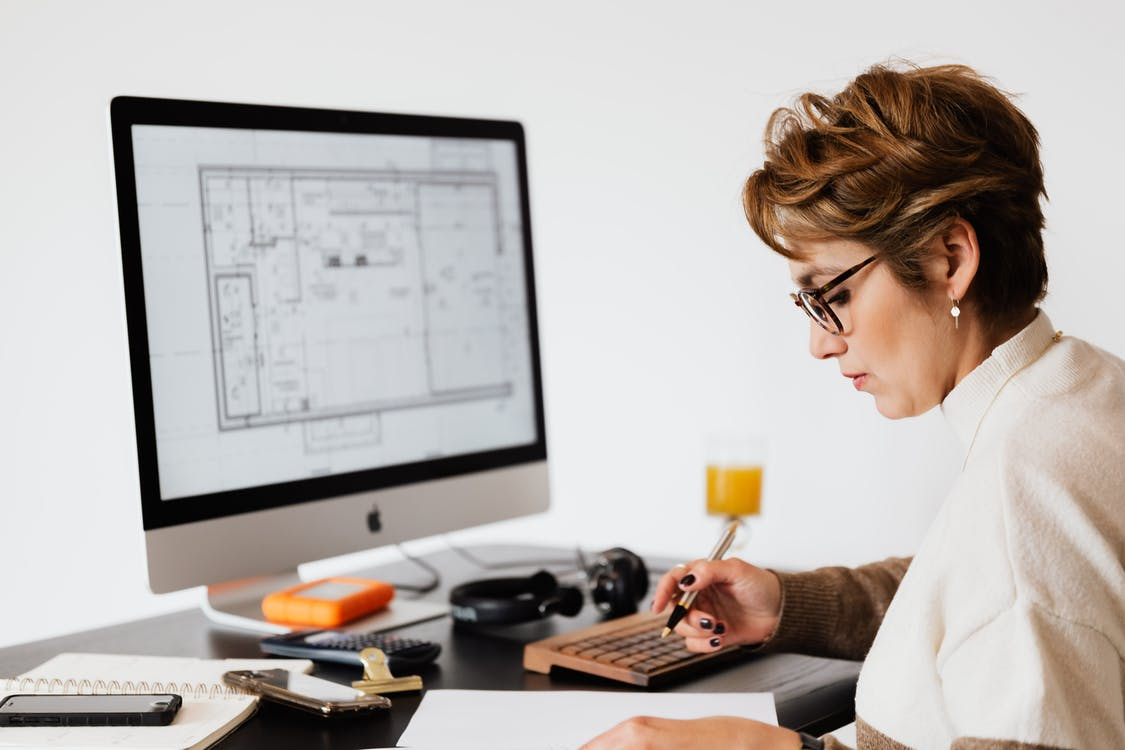 Focused woman editing paper documents during work at desk with computer