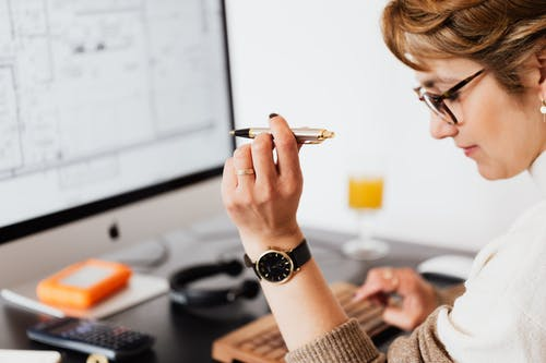 Side view of crop focused businesswoman in eyeglasses with pen in hand making report of financial results while working on computer
