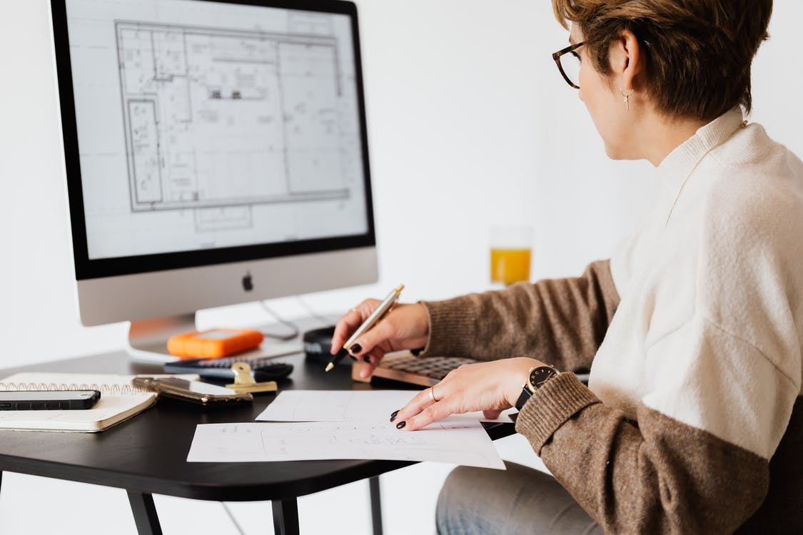 Crop estate agent working with computer in office