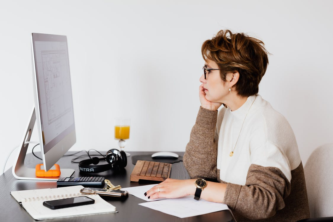 Side view of elegant female architect in glasses sitting at desk with modern PC and studying plan of building on computer screen