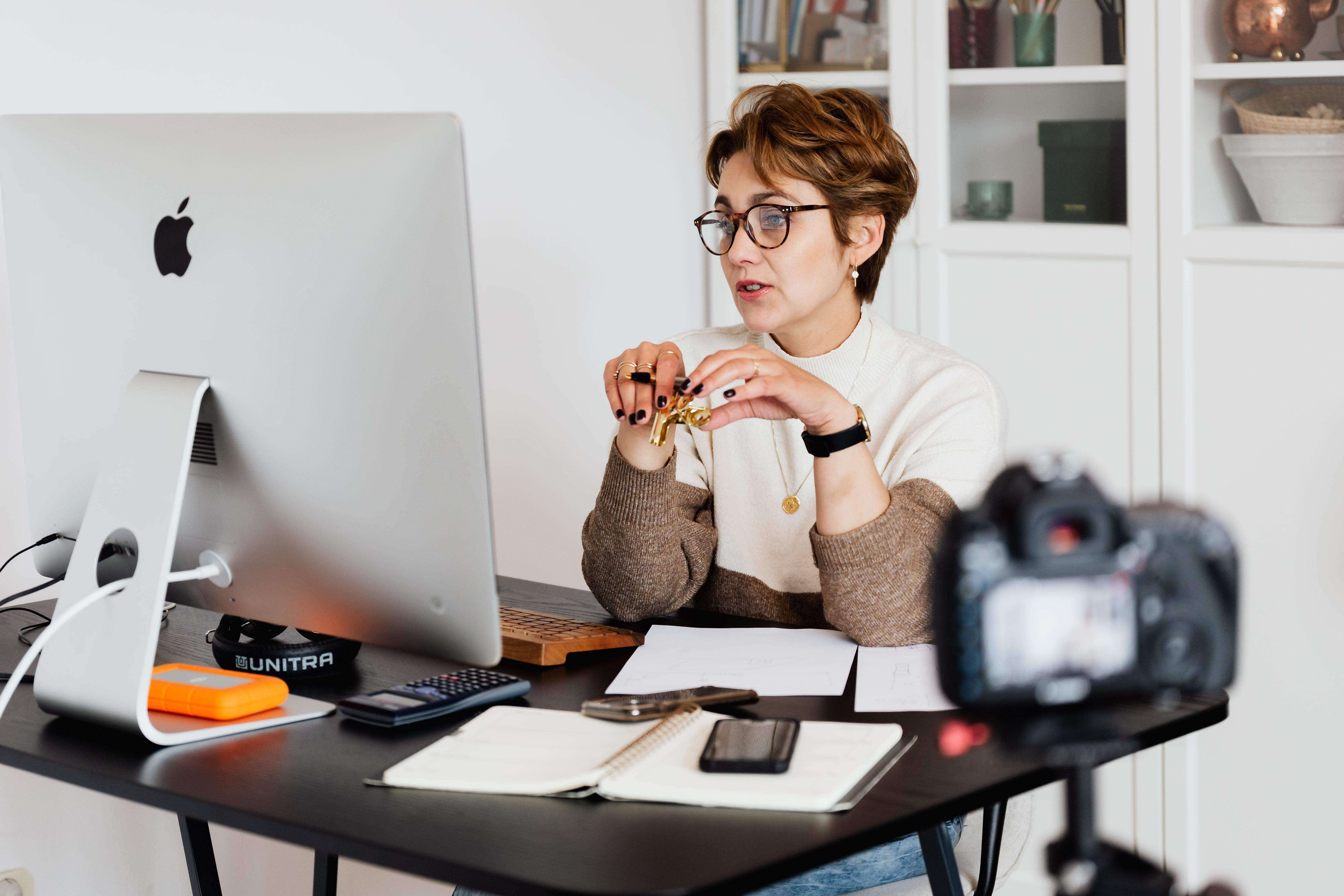 Lady in eyeglasses hosting webinar - Hotcopy