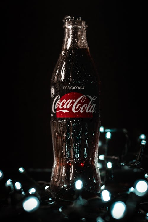 Bottle of refreshing soft drink on table near glowing lamps