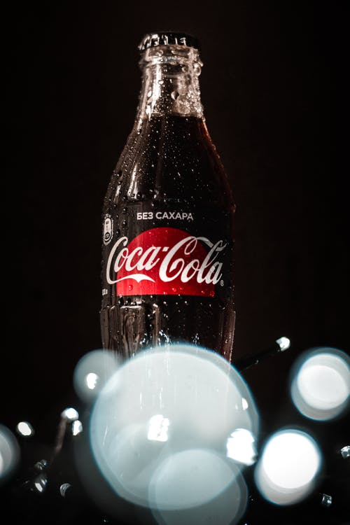 Low angle wet glass bottle of fizzy soda drink placed on table in dark room near fairy lights