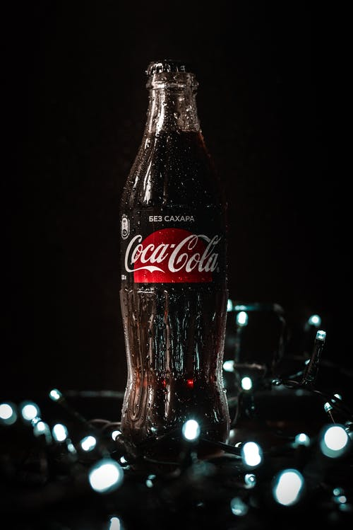 Cold glass bottle of refreshing soda arranged with glowing Christmas garlands on black table