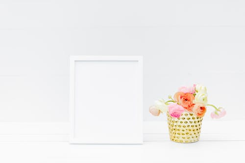 White Wooden Frame Beside Yellow and Pink Flowers in White Ceramic Vase