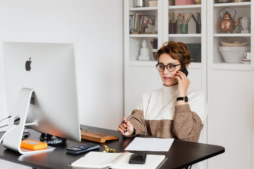 Smart confident female managing director listening to employees report on smartphone while working on computer in light modern office