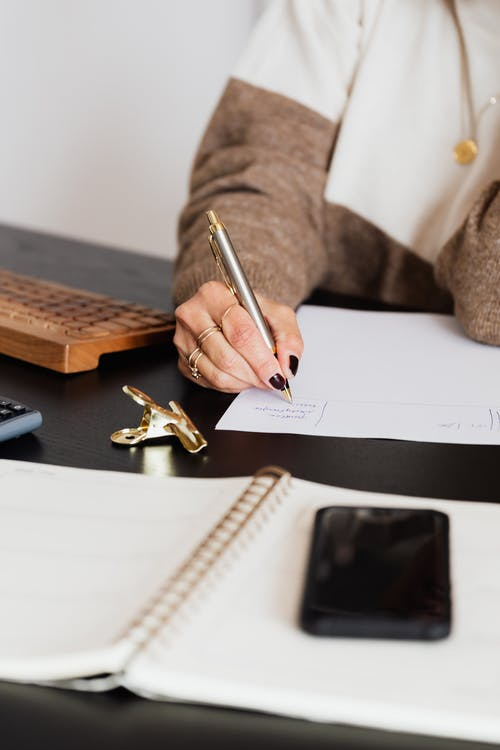 Unrecognizable female entrepreneur writing on piece of paper while sitting at table with notebook and smartphone