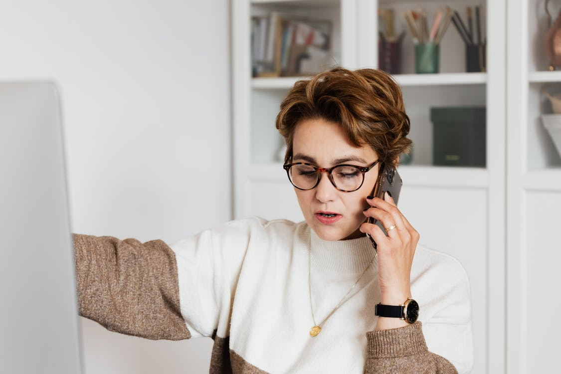 Female remote worker in eyeglasses talking on mobile with boss while working on project at home
