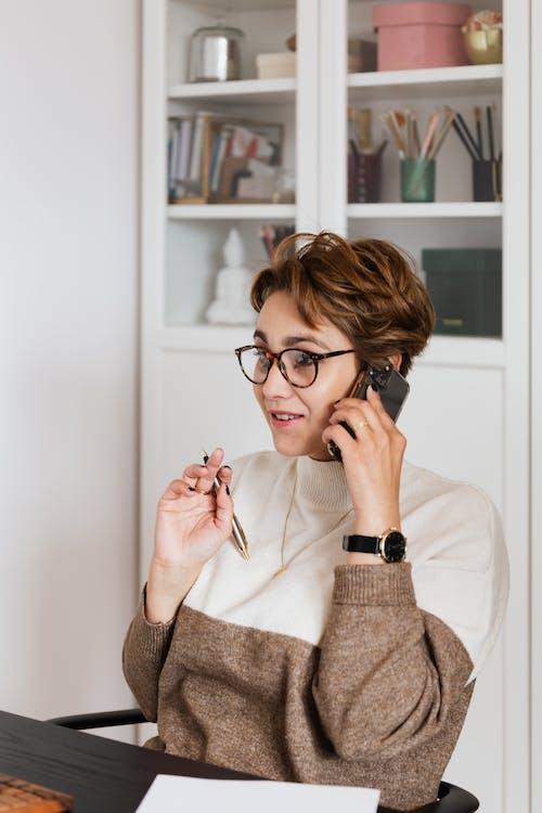 Positive office worker talking on mobile phone sitting at desk