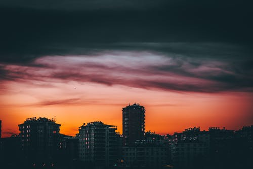 Picturesque scenery of colorful cloudy sunset sky over modern city district with contemporary buildings