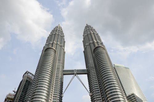 From below tall futuristic twin towers with steel and glass facade located against cloudy sky in Kuala Lumpur