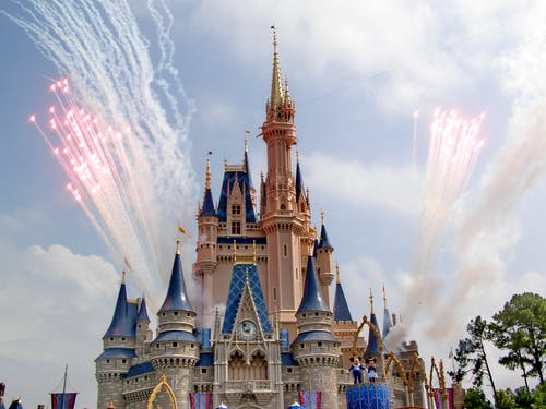 Amazing princess castle with colorful ornamental details located in amusement park during fireworks
