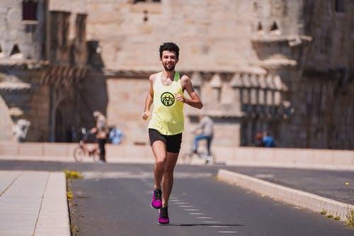 Full body of happy young male athlete in sportswear running on asphalt path against ancient castle during outdoor fitness training