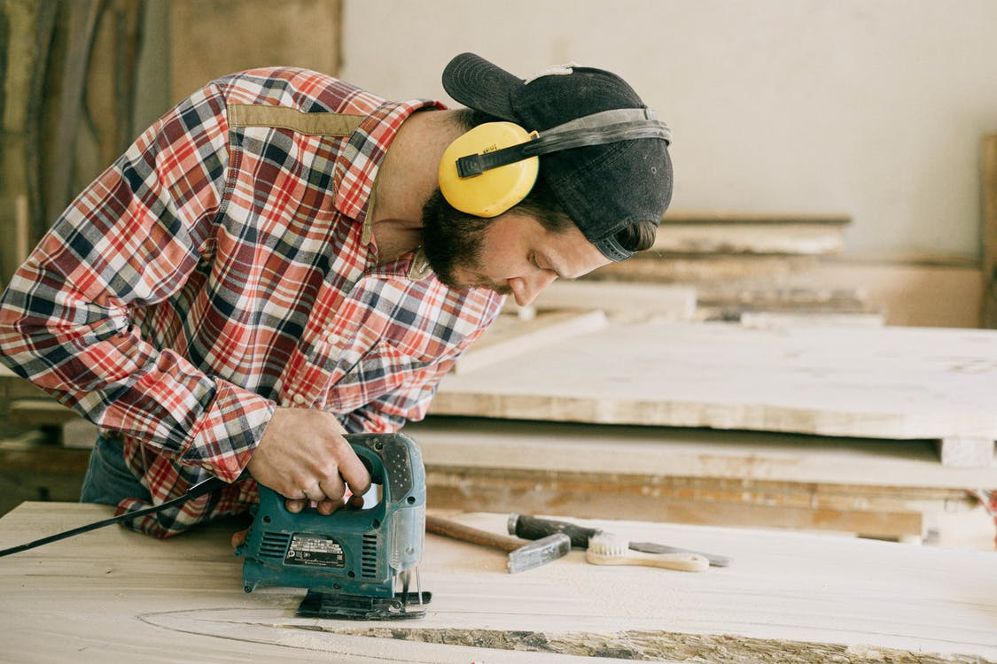 Man in Red White and Black Plaid Dress Shirt Wearing Yellow Hard Hat Holding Green Power