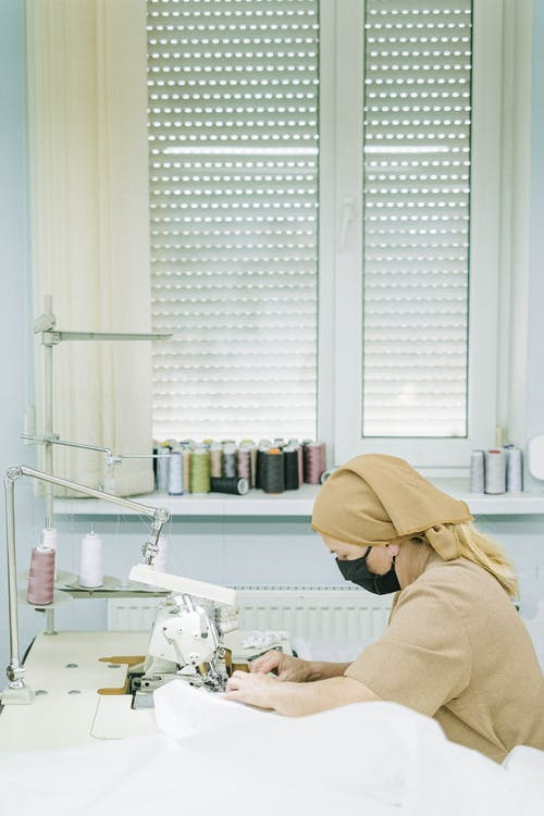 Person in Brown Hoodie Standing in Front of White Sewing Machine