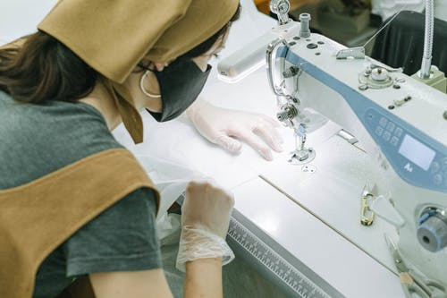 Person in Green Shirt Holding White Sewing Machine