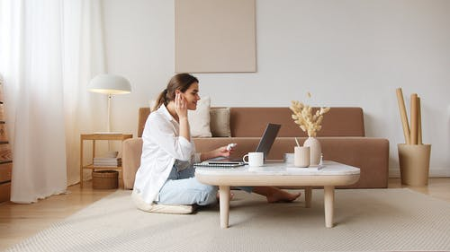 Cheerful woman with earbuds listening to music and using laptop
