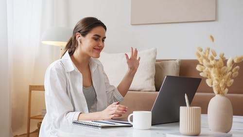 Cheerful woman having video call via laptop