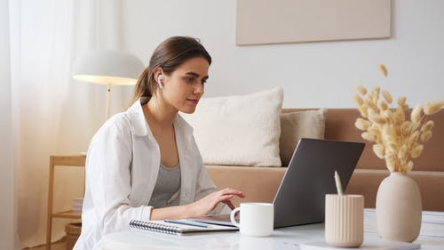 Thoughtful woman with earbuds using laptop