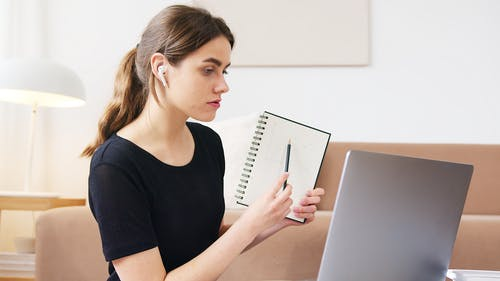 Young student with notebook attending online lesson