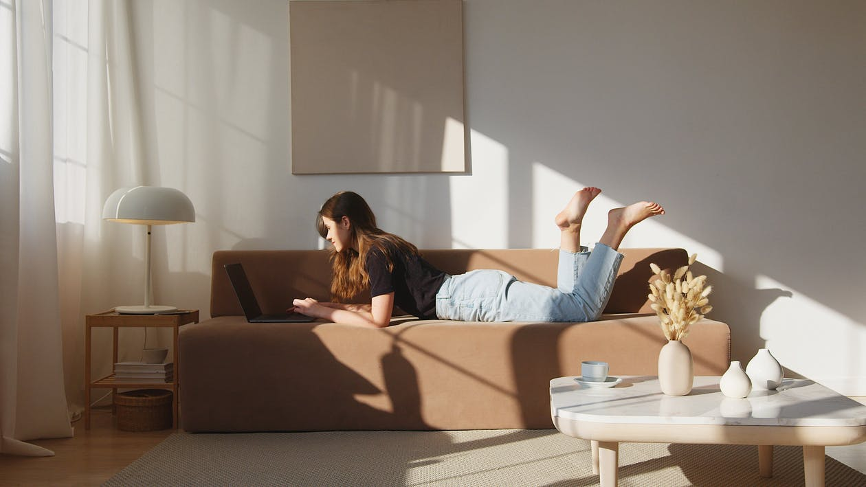 Side view full body young lady in casual outfit lying on comfortable couch and browsing netbook in cozy modern living room