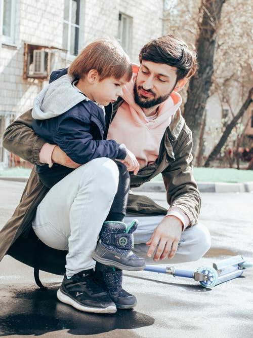 Father and son playing together on street