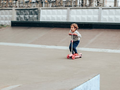 Amazed little boy riding kickboard scooter in skate park