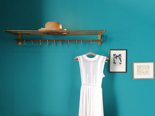 Hanger with straw hat and white dress near blue wall