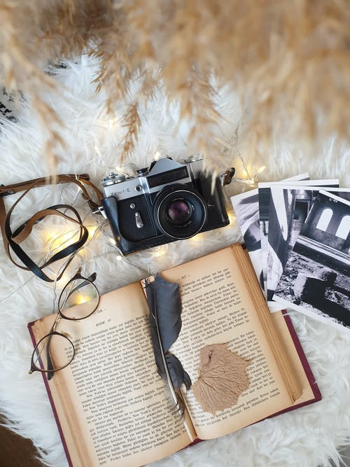 Retro camera and photos placed on carpet with book and eyeglasses
