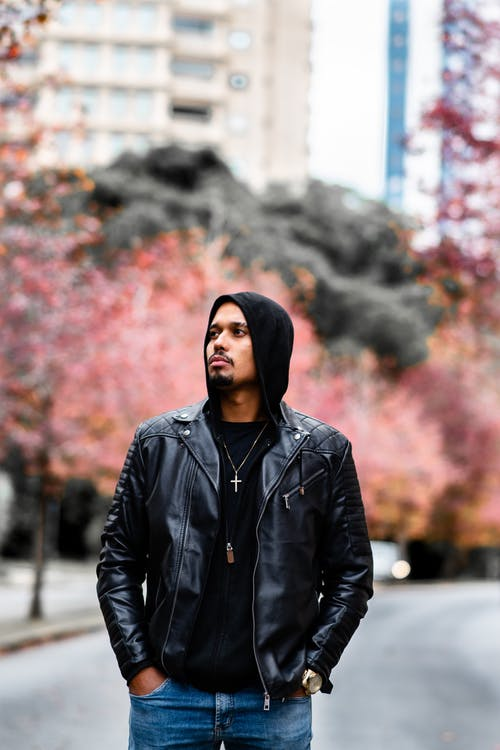 Confident young ethnic bearded male in trendy leather jacket and hoodie standing on street with hands in pockets and looking away in autumn