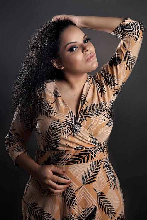 Sensual young ethnic female in stylish dress touching long curly hair and looking at camera against gray background
