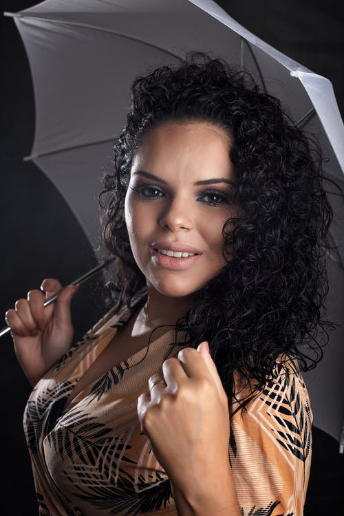 Content young ethnic lady holding umbrella and looking at camera