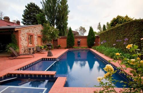 Big blue swimming pool in yard of small brick private house decorated with tall green hedgerows and blooming flowers