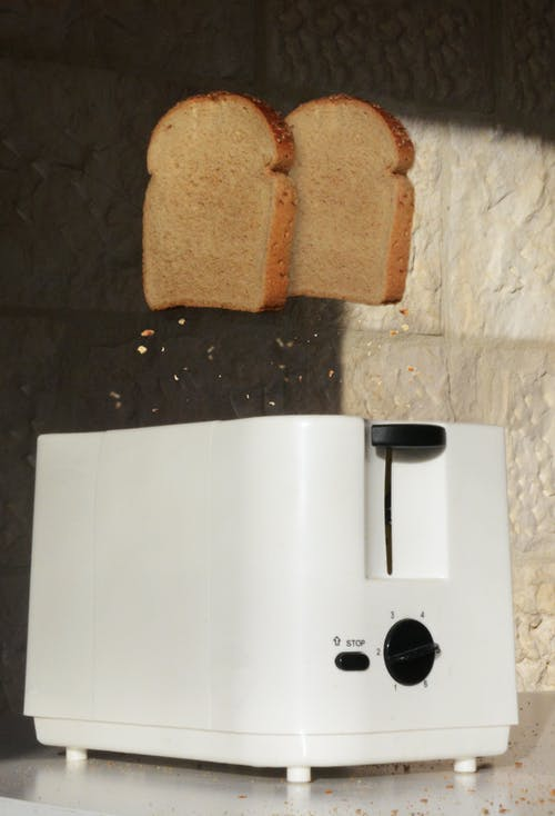 Pieces of fried rye bread popping up from white modern toaster on table in bright kitchen