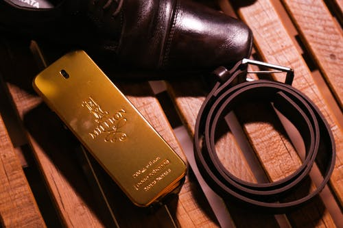 Elegant black luxury glossy man shoes and belt composing with perfume in bottle in form of gold bar on wooden bench