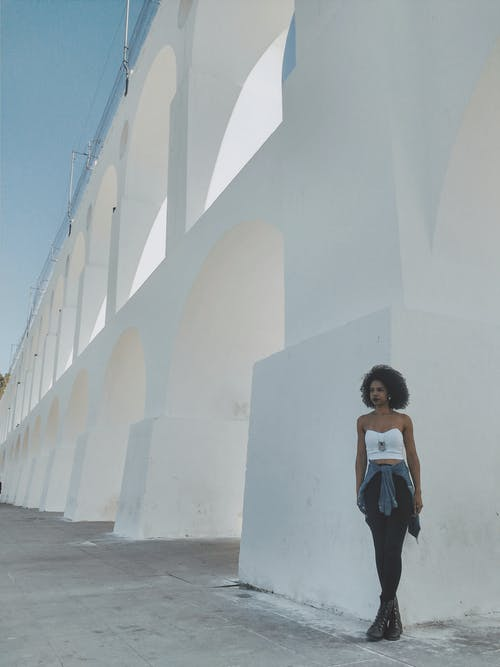Woman in Black and White Tank Top and Black Skirt Standing on White Concrete Building during