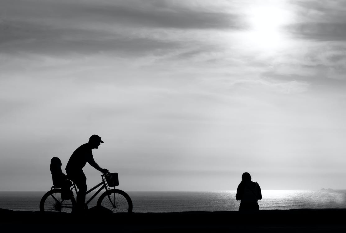 Silhouette of Man Riding Bicycle Near Body of Water