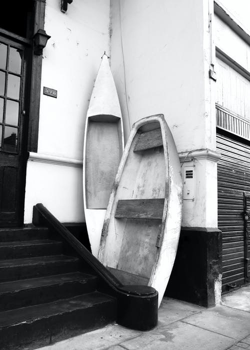 White and Black Wooden Boat on Black Wooden Stairs