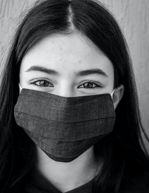 Positive young woman in face mask