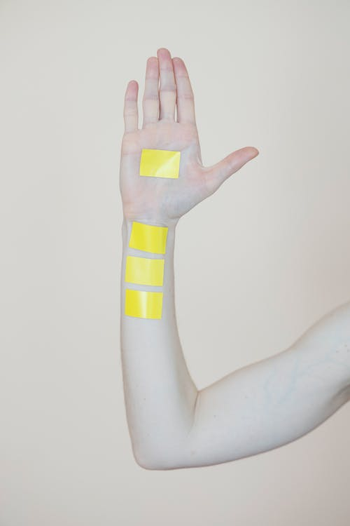 Person Holding Yellow and White Plastic Toy