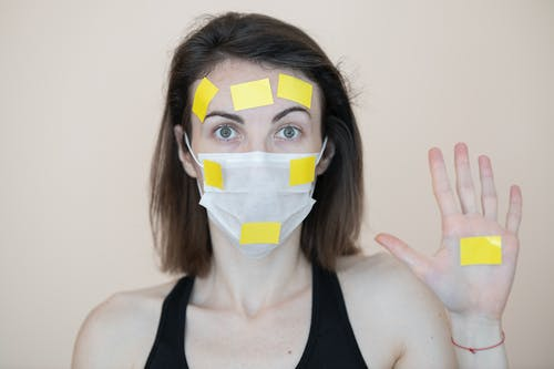 Woman in Black Tank Top With White and Blue Mask