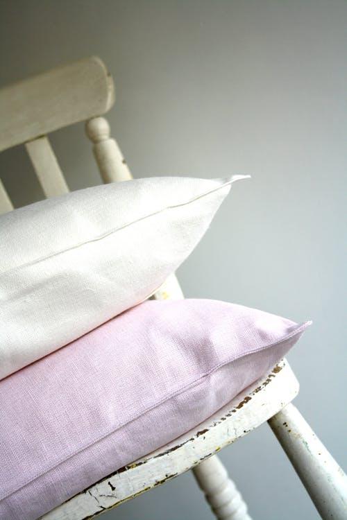 White and Pink Pillows on Top of White Wooden Chair