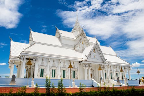 White temple under blue sky with clouds