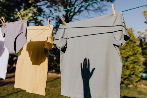 Clothes drying on rope with clothespins in garden