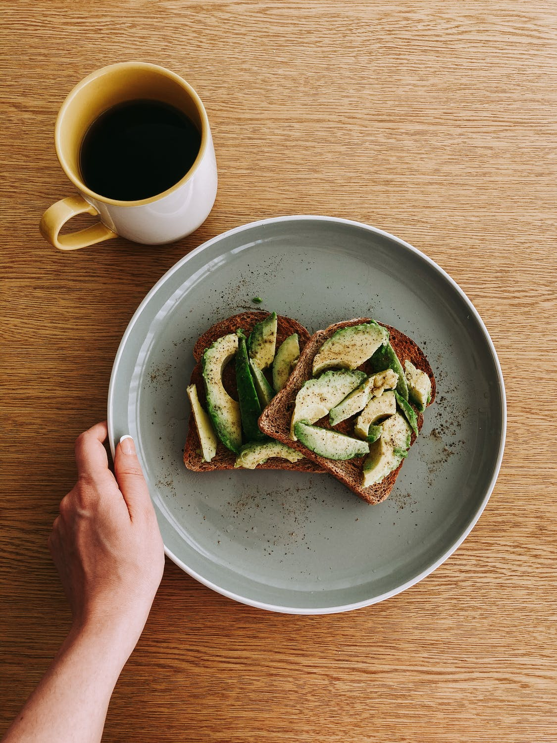 mug of black coffee and avocado on toast