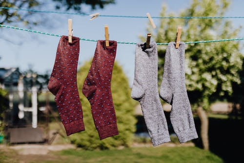 Soft focus of washed multicolored socks hanging on rope with clothespins outdoors on sunny summer day against natural background