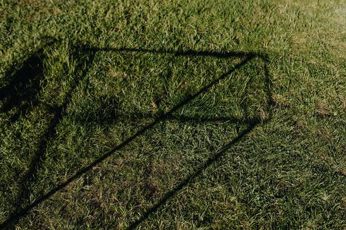 From above of green lawn with abstract shadow drawing on grass on sunny day