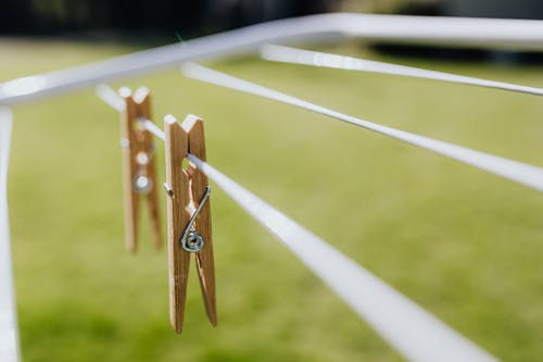 Metall clotheshorse with clothespins on green lawn