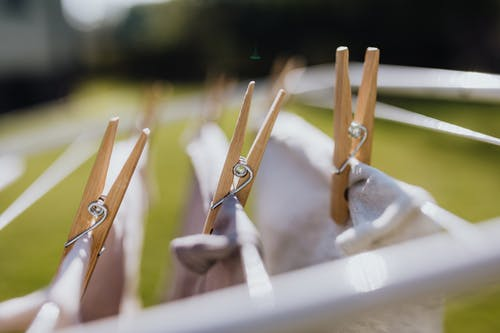 Wooden clothespins with wet underwear drying on metal collapsible clotheshorse on green meadow