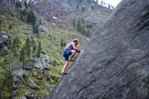 Man Climbing on Rock Mountain